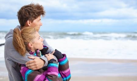 warm clothes: Coppia abbracciare e divertirsi indossando vestiti caldi fuori sulla costa dietro il cielo blu Archivio Fotografico