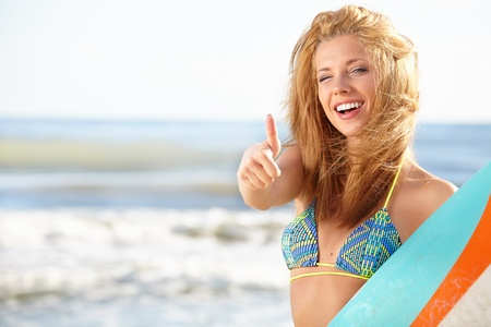 Beautiful sexy young woman surfer girl in bikini with surfboard at a beach  photo