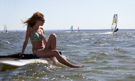 young beautiful woman on windsurfing in water photo