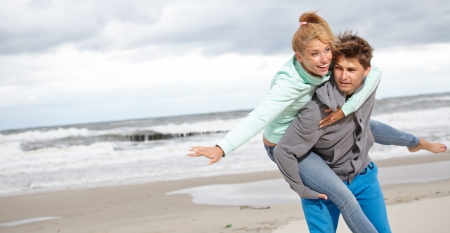 offset view: Couple running on beach holding hands smiling  Stock Photo