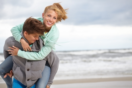 winter couple: Couple running on beach holding hands smiling  Stock Photo