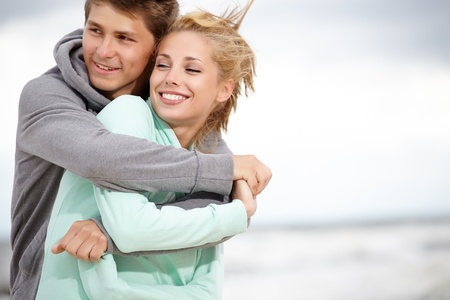 winter day: Couple running on beach holding hands smiling  Stock Photo