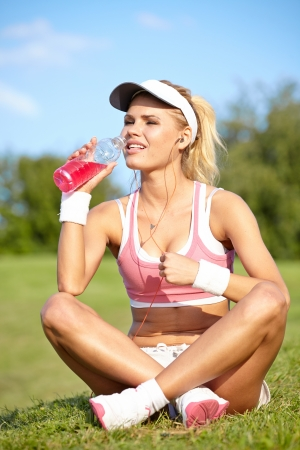 sports bra: Stunning young blonde woman in pink sports bra rests while holding a water bottle and adjusting music on portable music player
