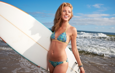 blue toned: Women standing on the beach holding a surfboard  Stock Photo