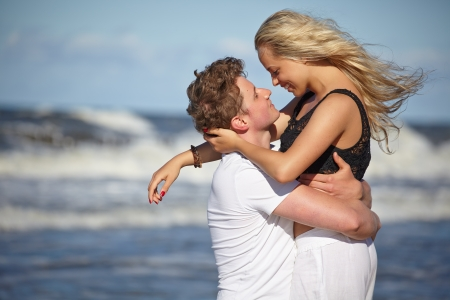 first love: Close up portrait of romantic kiss on beach.