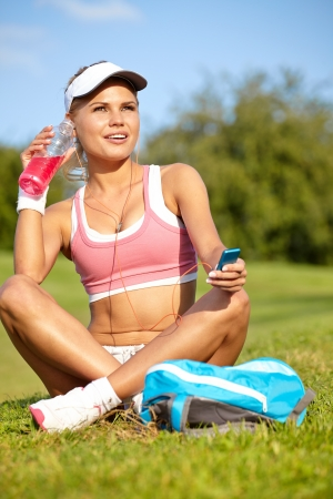 Stunning young blonde woman in pink sports bra rests while holding a water bottle and adjusting music on portable music player