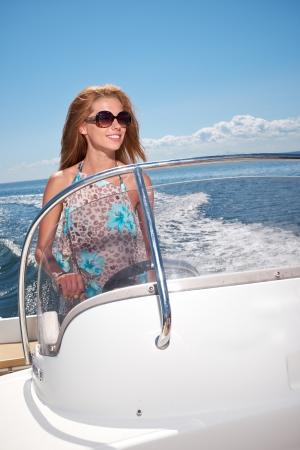 Summer vacation - young girl driving a motor boat  photo