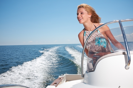 motors: Summer vacation - young girl driving a motor boat