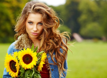 Young fashion woman with a bouquet of sunflowers in the field  photo