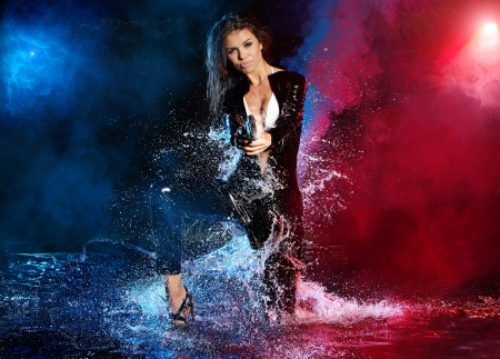 deadly: beautiful sexy girl holding gun in water. smoke background  Stock Photo