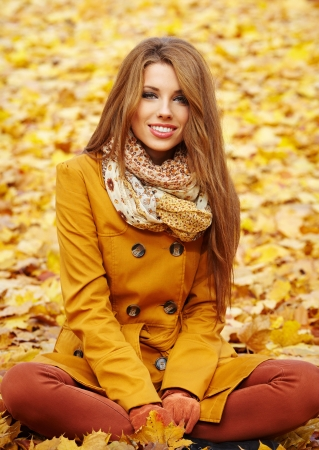 russian woman: Young woman with autumn leaves in hand and fall yellow maple garden background
