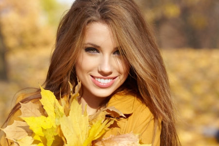 Beautiful autumn woman in golden park photo
