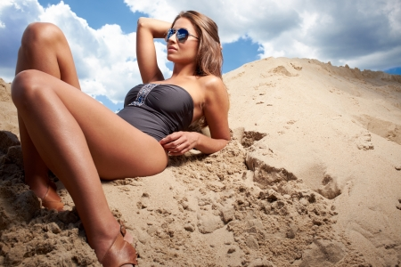 Romantic relaxed woman in bikini on sand sunbathing and resting  photo