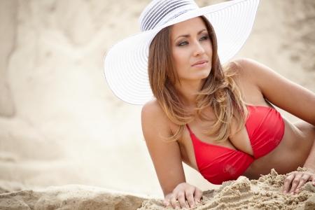 Beautiful young woman in bikini on a sunny beach.  photo
