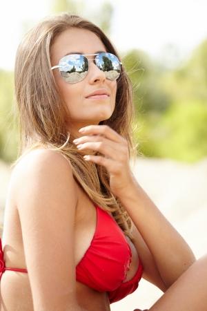 Young beautiful woman in red bikini and sunglasses at beach  photo