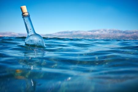 isla flotante: Botella con un mensaje en el agua Foto de archivo