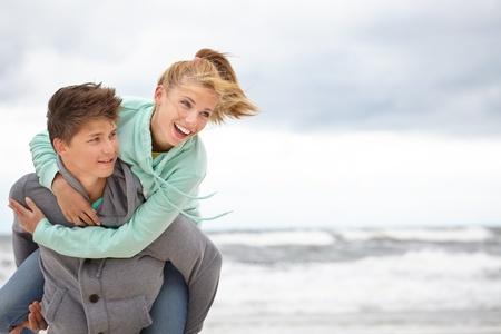 pareja abrazada: Pares que abrazan y que se divierten usando ropa de abrigo al aire libre en la costa detr�s de cielo azul Foto de archivo