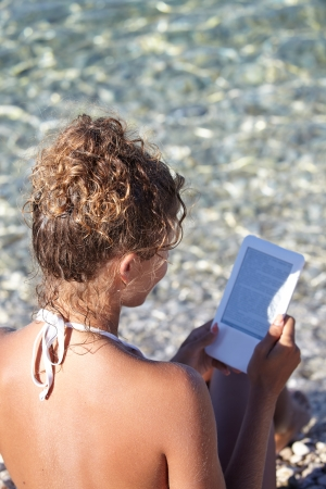 ereader: Woman with an e-reader on vacation at the beach reading a book