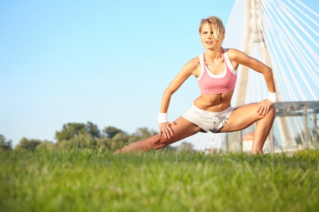 woman stretching hamstring leg muscles during outdoor running workout   photo