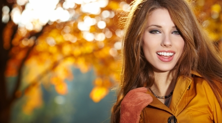 long haired: Young woman with autumn leaves in hand and fall yellow maple garden background