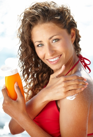 lotions: woman applying suntan lotion at the beach smiling