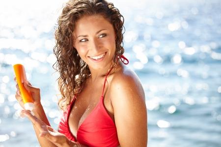 woman applying suntan lotion at the beach smiling  photo