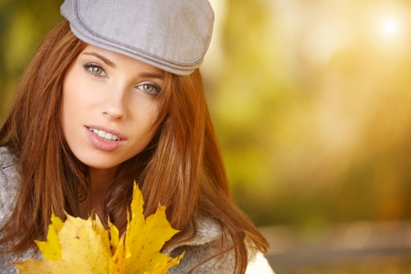 happy fall woman smiling joyful and blissful holding autumn leaves outside in colorful fall forest   Stock Photo - 23182973