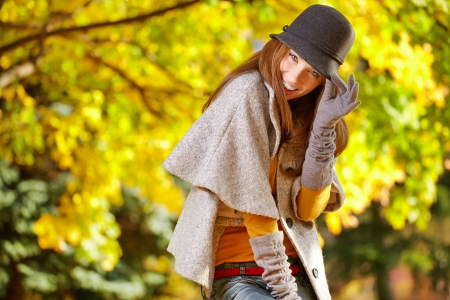 Fashionable woman with autumn leaves in hand and fall yellow maple garden background  photo