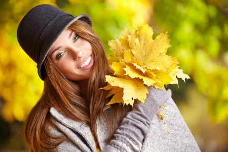 happy fall woman smiling joyful and blissful holding autumn leaves outside in colorful fall forest   photo