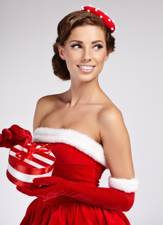 sexy housewife: Christmas vintage brunette with gift box, isolated on grey  Fashion in retro style