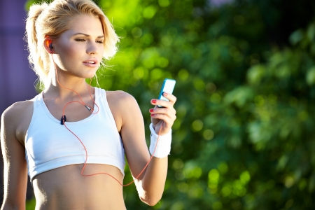 woman in white  sports bra rests while adjusting music on portable music player  Stock Photo