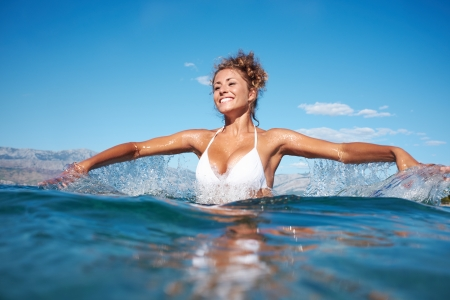 Beautiful young woman in the sea splashing water  photo
