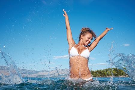 spruzzi acqua: Bella giovane donna in acqua spruzzi del mare Archivio Fotografico