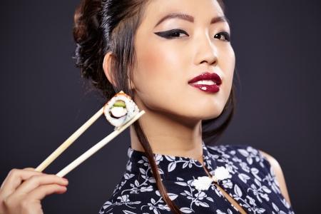 model fish: Young beautiful asian woman eating sushi,