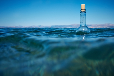 Bottle with a message in water  photo
