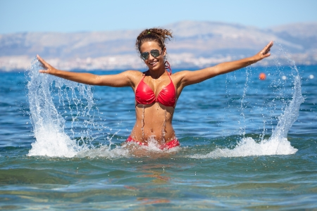 playing in the sea: Attractive girl playing in the sea with a splash of water Stock Photo