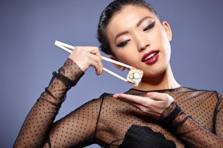 Sushi woman holding sushi with chopsticks photo