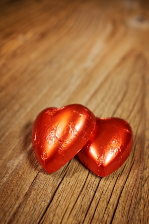 praline: Delicious chocolate hearts on old wood table- focus on heart-shaped praline