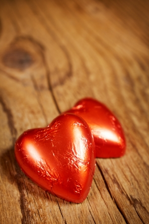 Delicious chocolate hearts on old wood table- focus on heart-shaped praline  photo
