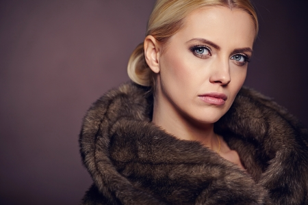 Portrait of beautiful young woman wearing fashionable fur , looking at camera.  photo