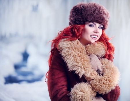 fashion portrait of a beautiful smiling girl with red hair in the winter  photo