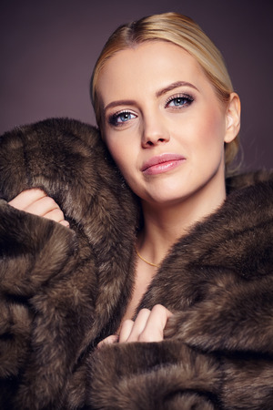 Portrait of beautiful young woman wearing fashionable fur , looking at camera   photo