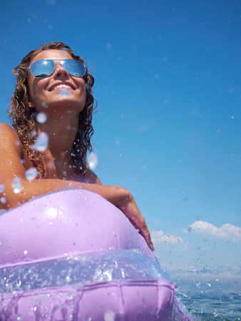 colorfully: Young perfect woman on an air mattress in the sea  Stock Photo