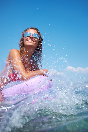 very happy woman on pink air bed in sea photo