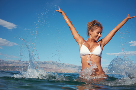 Happy young woman in sea with open hands   photo