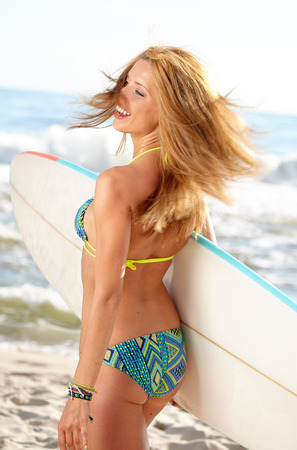Beautiful Young Woman Surfer Girl in Bikini with Surfboard at a Beach  photo
