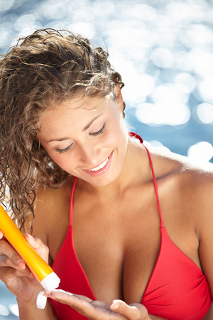 Sunscreen beach woman in bikini applying sun block solar cream for UV protection. photo