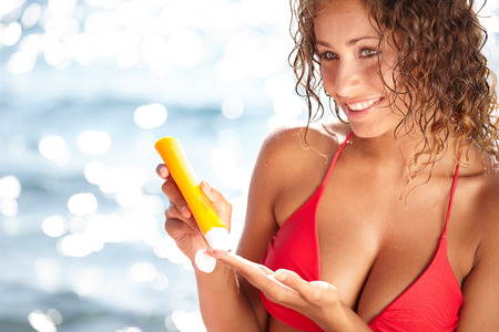 Sunscreen beach woman in bikini applying sun block solar cream for UV protection. photo