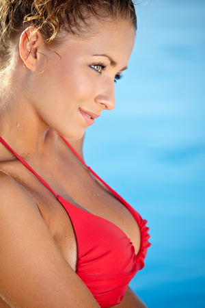 Gorgeous woman in a red bikini standing in the water at the edge of a pool enjoying the sun  photo