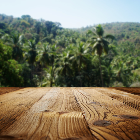 wooden table on the beach with palms Stock Photo
